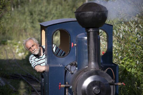 Павел Чилин ведет свой паровоз по собственной миниатюрной личной железной дороге в селе Ульяновка под Санкт-Петербургом - Sputnik Беларусь