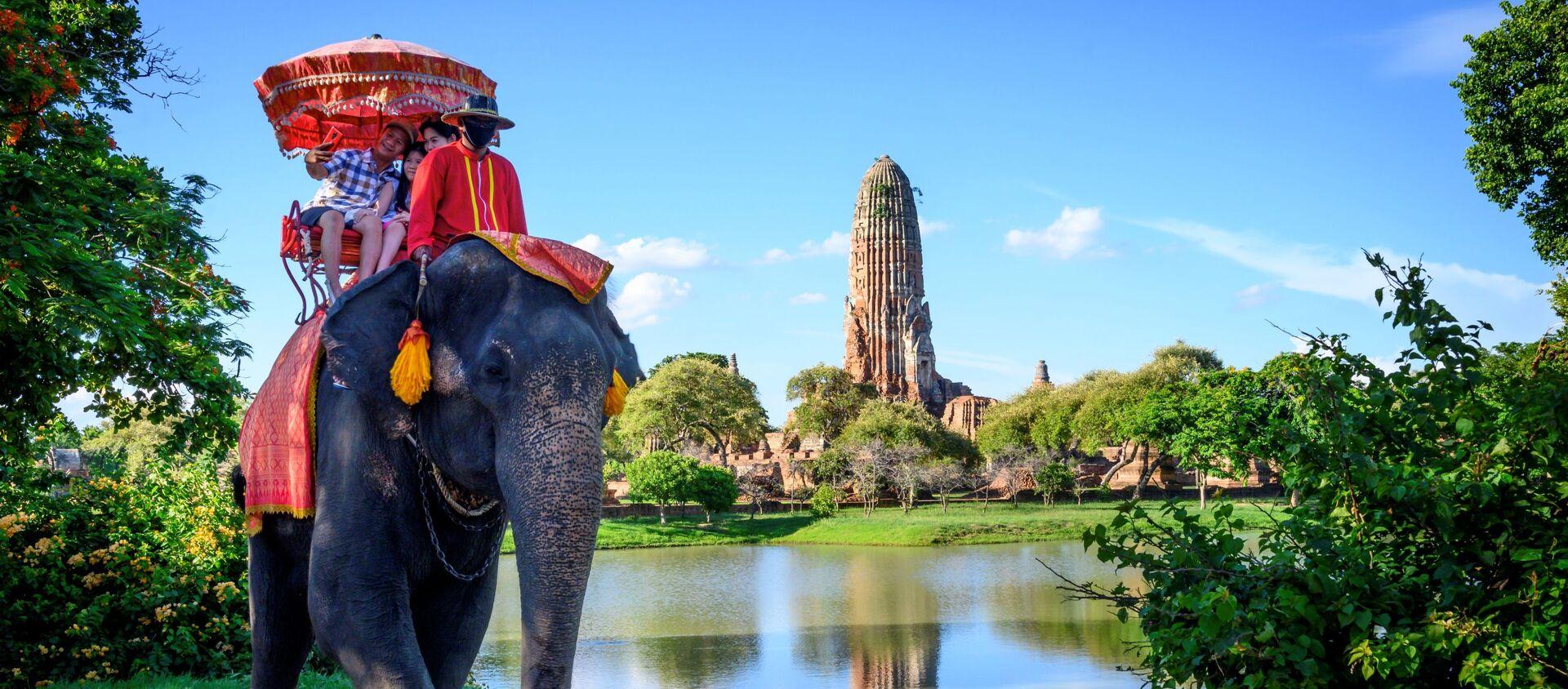 Туристы едут на слоне перед старым буддийским храмом в Аюттхае, примерно в 70 км к северу от Бангкока, Таиланд - Sputnik Беларусь, 1920, 08.03.2021