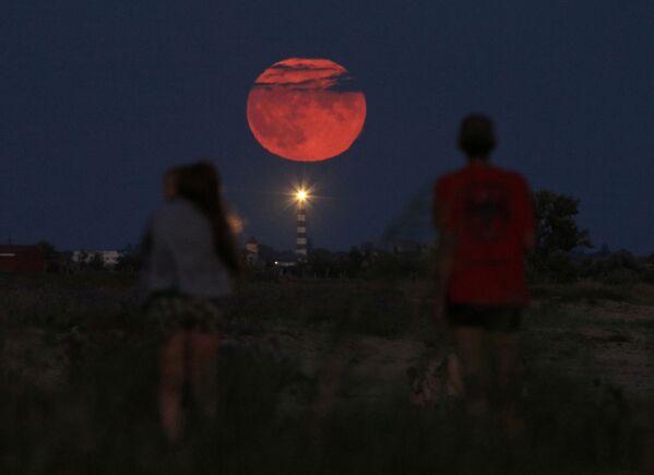 Люди наблюдают за полнолунием, поднимающимся над маяком возле села Молочное, Крым - Sputnik Беларусь