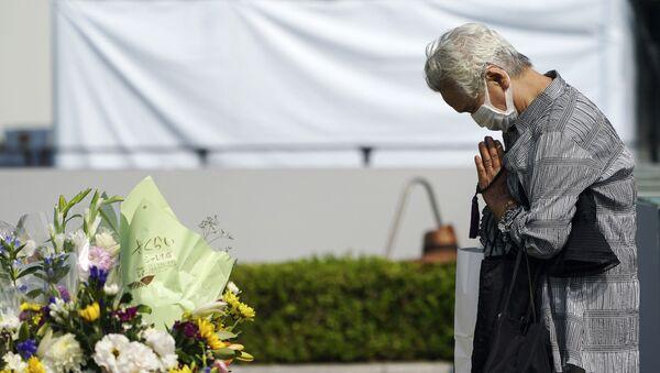 Посетитель молится перед кенотафом о жертвах атомной бомбардировки возле Хиросимского мемориального музея мира - Sputnik Беларусь