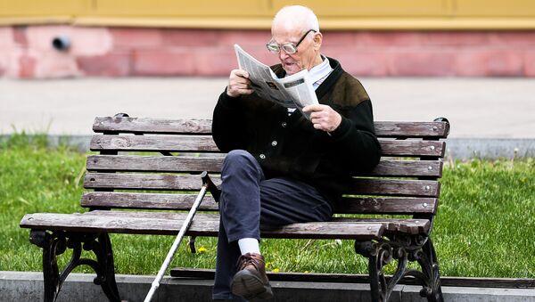 Мужчина читает газету на улице на лавочке  - Sputnik Беларусь