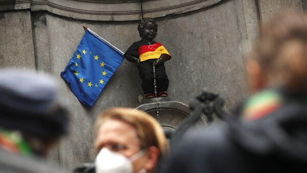 Скульптура Писающий мальчик, одетый в цвета немецкого флага, рядом с флагом ЕС в центре Брюсселя - Sputnik Беларусь