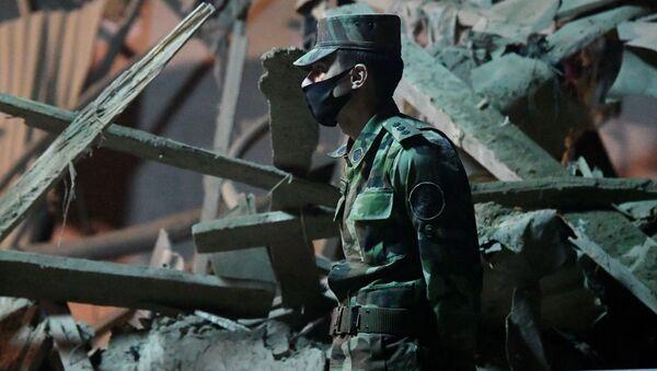 Военнослужащий на месте разбора завалов разрушенных домов после ракетного обстрела города Гянджа - Sputnik Беларусь