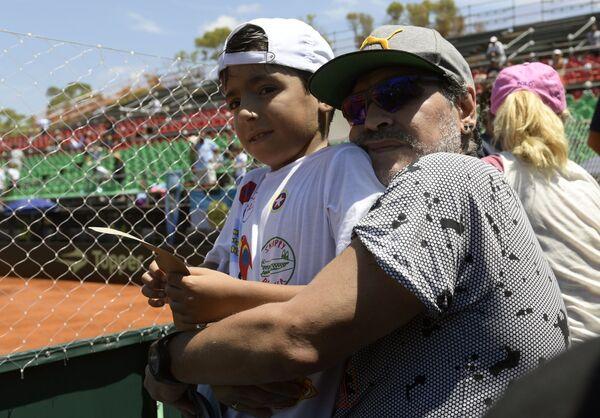 Марадона с внуком на теннисном матче в Буэнос-Айресе. Бенхамин - сын футболиста Серхио Агуэро и дочери Джаннины, крестник  Лионеля Месси. Его родители развелись после 4 лет брака, за что Марадона возненавидел зятя и назвал его слабаком.  - Sputnik Беларусь