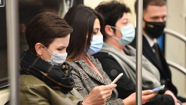 Люди в защитных масках в вагоне Московского метрополитена - Sputnik Беларусь