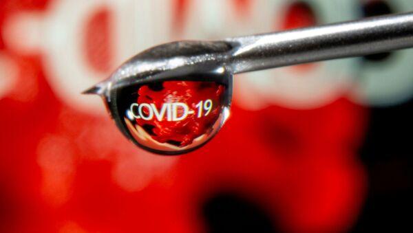 Слово COVID-19 отражается в капле на игле шприца - Sputnik Беларусь