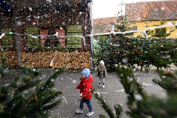 Дзеці гуляюць са штучнымі сняжынкамі на калядным кірмашы ў Германіі. - Sputnik Беларусь