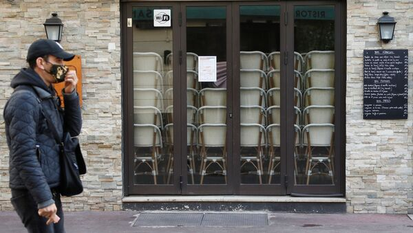 Мужчина идет мимо закрытого из-за пандемии коронавируса ресторана во Франции - Sputnik Беларусь