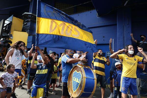 Фанаты легенды аргентинского футбола Диего Марадоны поют возле стадиона Ла Бомбонера в районе Ла-Бока в Буэнос-Айресе - Sputnik Беларусь