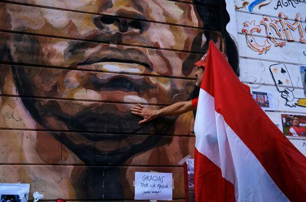 Фанат с перуанским флагом оплакивает смерть легенды футбола Диего Марадоны  - Sputnik Беларусь