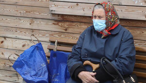 Пожилая женщина отдыхает на скамейке - Sputnik Беларусь