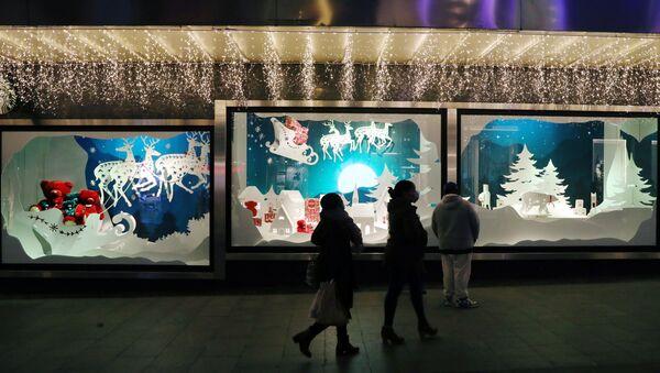 Люди проходят мимо рождественских украшений витрины в Мадриде - Sputnik Беларусь