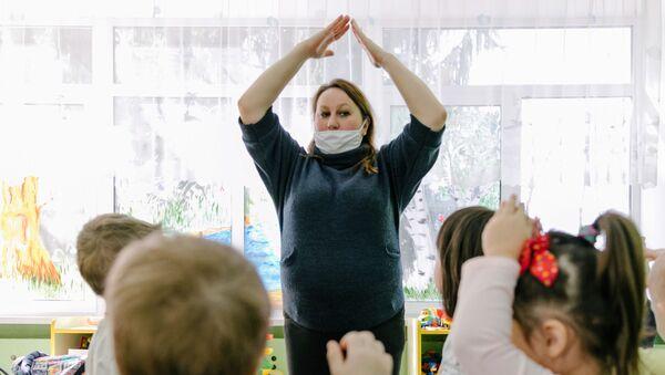Воспитатель в медицинской маске играет с детьми в детском саду - Sputnik Беларусь