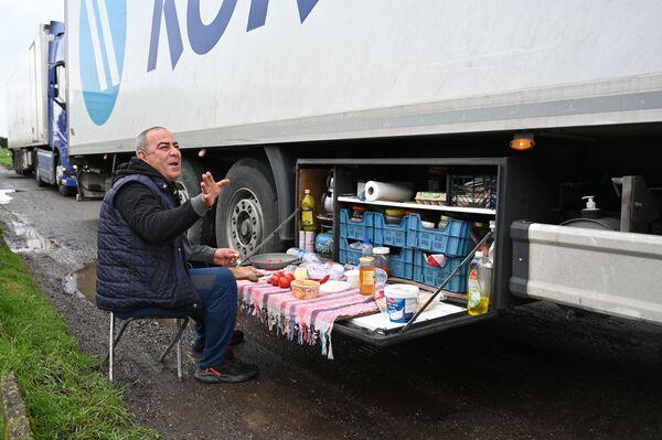 Турецкий водитель-дальнобойщик завтракает на стоянке для грузовиков у автомагистрали M20 на юго-востоке Англии - Sputnik Беларусь