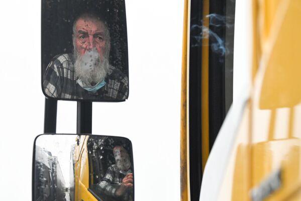 Венгерский водитель грузовика курит, ожидая на международной остановке грузовиков в Эшфорде - Sputnik Беларусь