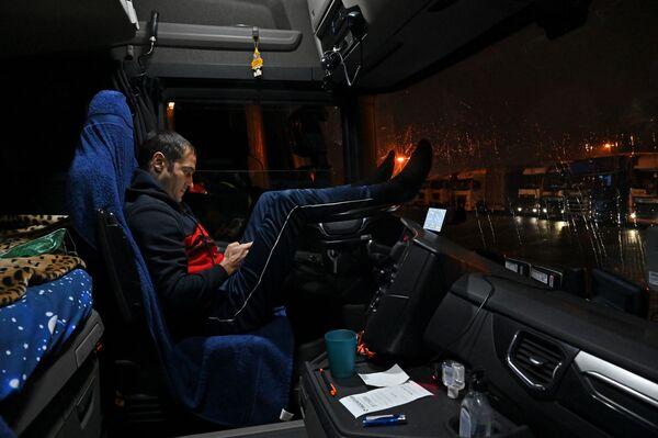 Румынский водитель сидит в кабине своего грузового грузовика, припаркованного на стоянке у автомагистрали M20, ведущей в Дувр - Sputnik Беларусь