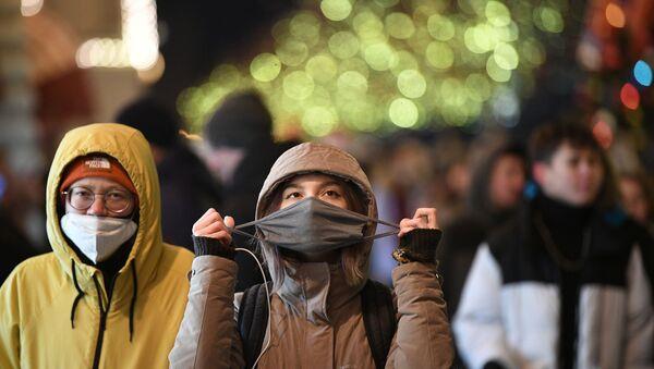Прохожие в защитных масках на украшенной к Новому Году Красной площади в Москве - Sputnik Беларусь