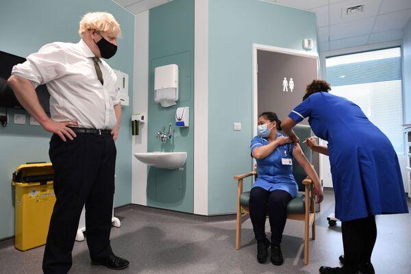 Прэм'ер-міністр Вялікабрытаніі Барыс Джонсан назірае за вакцынацыяй падчас свайго візіту ў бальніцу Chase Farm на поўначы Лондана - Sputnik Беларусь