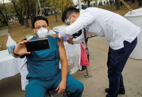 Медыцынскі работнік робіць сэлфі падчас ін'екцыі вакцыны ад COVID-19 у ваенным шпіталі ў Сан-Нікалас-дэ-лас-Гарсія, Мексіка - Sputnik Беларусь