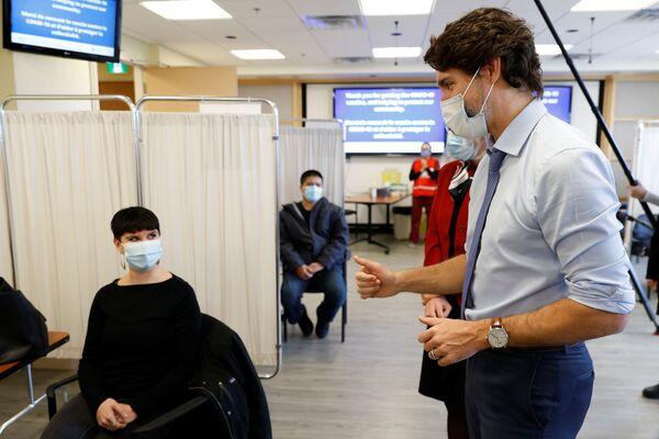 Прэм'ер-міністр Канады Джасцін Трудо размаўляе з пацыентам пасля таго, як ён атрымаў адну з першых прышчэпак ад COVID-19 у шпіталі ў Атаве - Sputnik Беларусь