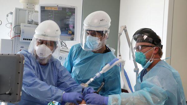 Врачи осматривают пациента в коронавирусном госпитале в Калифорнии - Sputnik Беларусь