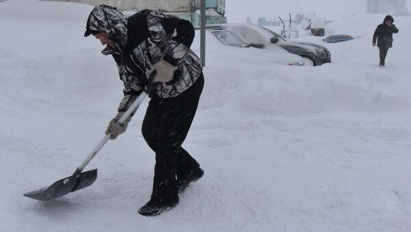 Мужчына расчышчае снег падчас снегападу ў двары жылога дома - Sputnik Беларусь