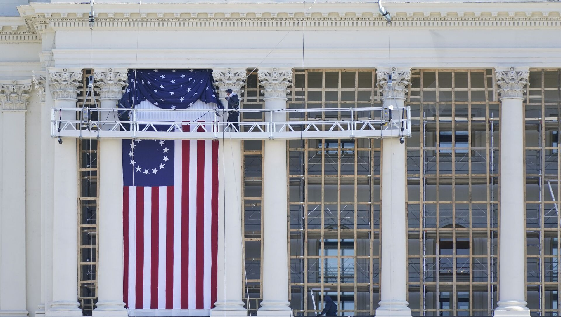 Рабочие устанавливают флаг на Капитолии во время подготовки к инаугурации избранного президента Джо Байдена - Sputnik Беларусь, 1920, 03.03.2021