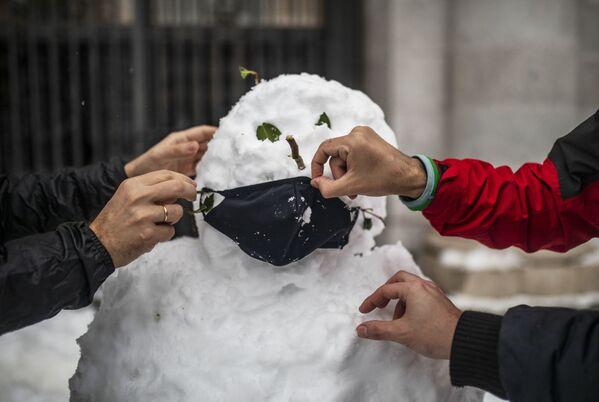 Люди надевают маску на слепленного снеговика на одной из улиц в Мадриде - Sputnik Беларусь