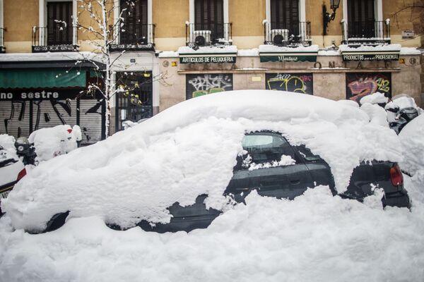Занесенный снегом автомобиль на одной из улиц в Мадриде - Sputnik Беларусь