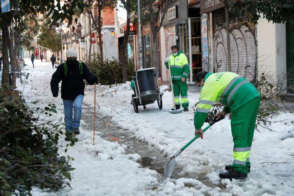 Сотрудники коммунальных служб убирают последствий снегопада на одной из улиц в Мадриде - Sputnik Беларусь