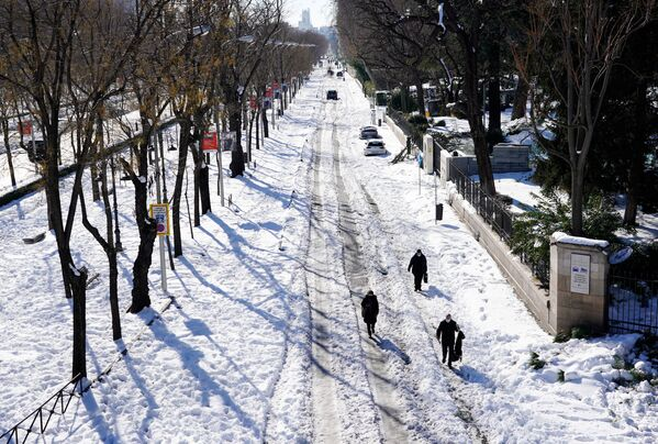 Люди идут по заснеженной улице после сильного снегопада в Мадриде - Sputnik Беларусь