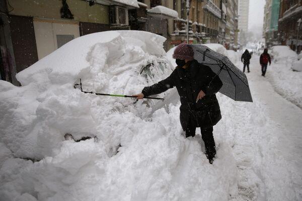 Женщина пытается убрать снег со своей машины в Мадриде - Sputnik Беларусь