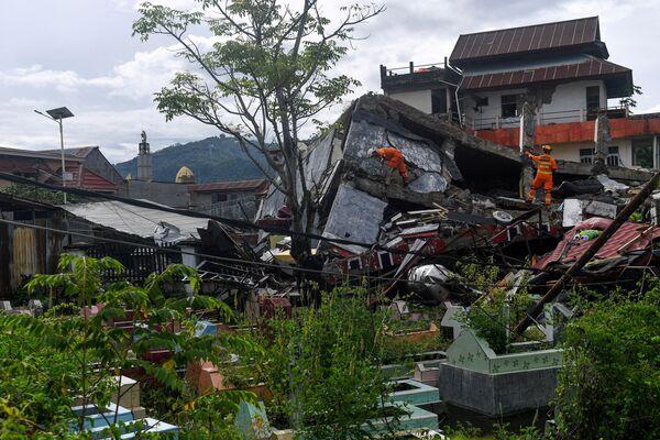 Поисково-спасательные службы осматривают разрушенное здание после землетрясения в Мамуджу - Sputnik Беларусь