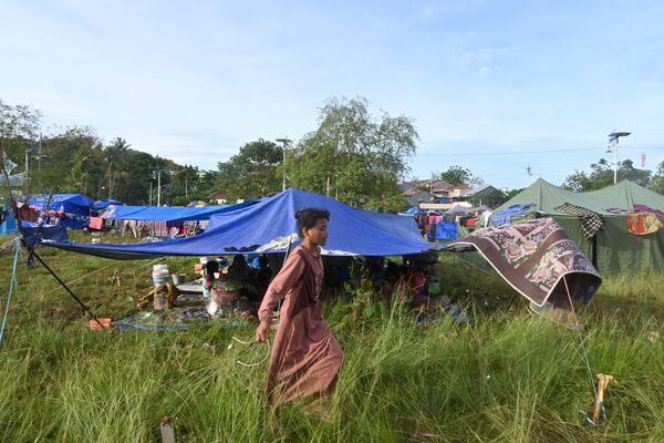 Девушка проходит мимо временного убежища для постадавших от землетрясения в Индонезии - Sputnik Беларусь