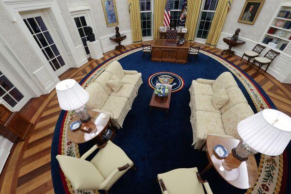 Новое убранство Овального кабинета Джо Байдена. Президент-демократ вернул золотистые шторы и синий (демократического цвета) ковер, которые появились здесь впервые при Билле Клинтоне. Как и многие предшественники, он сохранил стол, изготовленный еще в 1880 году из древесины корабля Резолют. Однако на столе появилась кружка и коробка с ручками. Трамп пил диетическую кока-колу, а ручкам предпочитал черные маркеры. - Sputnik Беларусь