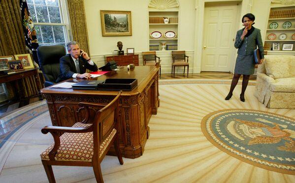Президент США Джордж Буш-младший и Госсекретарь США Кондолиза Райс в Овальном кабинете в Белом доме, 2003 год. Буш выбрал более приглушенную цветовую палитру, чем его предшественник, используя оттенки серо-коричневого и цвета морской волны. За дизайн ковра отвечала его жена Лора. - Sputnik Беларусь
