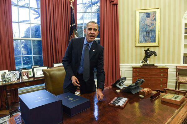Президент США Барака Обама в Овальном кабинете в Белом доме, 2015 год. Справа - та самая Авеню под дождем. Во время его первого срока кабинет был выдержан в спокойных тонах, позже там появились красные шторы. - Sputnik Беларусь