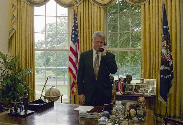 Президент Билл Клинтон разговаривает в Овальном кабинете по телефону, 1995 год. Скандальный кабинет Клинтона украшали несколько картин, в том числе Авеню под дождем Чайлда Фредерика Хассама, которую сейчас вернул Байден. Предметы искусства Белому дому во временное пользование предоставляются Национальной художественной галереей США. - Sputnik Беларусь