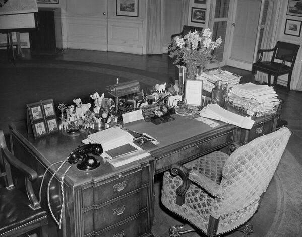 Стол президента Рузвельта в Белом доме в Вашингтоне был заставлен всевозможными предметами, среди которых фотографии его четырех сыновей в армии, две проволочные корзины, заваленные бумагами, множество миниатюрных фигурок ослов, собак, сувенир в виде штурвала, электрические часы, подставка для чернил, резак для бумаги, пепельницы, ваза с цветами, кувшин и стакан для воды, календарь и список встреч. - Sputnik Беларусь