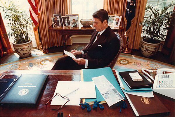 Президент США Рональд Рейган готовит речь за своим столом в Овальном кабинете, 1981 год. В 1982 году президент Рональд Рейган заменил паркет на полу на схожий по дизайну с эскизом Эрика Гуглера 1933 года, который так и не был установлен. А первая леди Нэнси Рейган во второй срок правления дополнила дизайн кабинета мужа новым ковром с узором в виде золотых лучей.  - Sputnik Беларусь