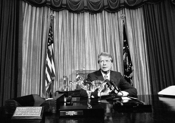 Президент США Джимми Картер на встрече с репортерами в Овальном кабинете в Вашингтоне, 1978 год. Картер вернул в офис стол Резолют, который не использовался на протяжении работы трех его предшественников — Линдона Джонсона, Ричарда Никсона и Джеральда Форда. Табличка на столе рассказывает историю стола, созданного из древесины британского судна. - Sputnik Беларусь