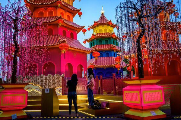 Дзяўчыны фатаграфуюцца ля святочнай інсталяцыі на фоне святлівых пагад каля гандлёвага цэнтра ў Бангкоку - Sputnik Беларусь
