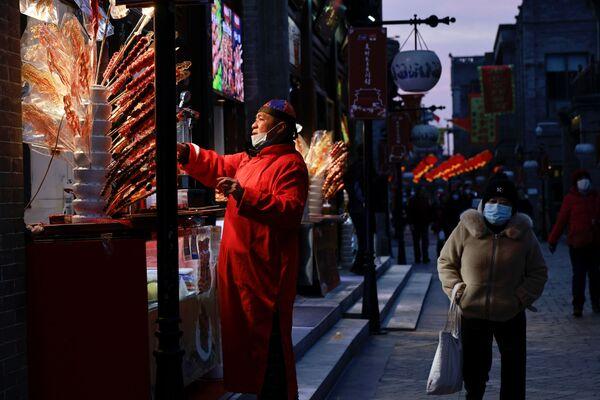 Гандляр прадае вулічную ежу Тангулу, традыцыйную паўночна-кітайскую закуску з зацукраванай садавіны, у Пекіне - Sputnik Беларусь