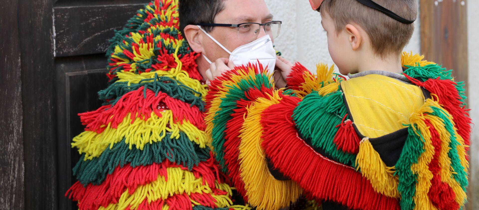 Мужчина с ребенком в традиционных костюмах карнавала, который был отменен из-за коронавируса в Испании - Sputnik Беларусь, 1920, 24.02.2021