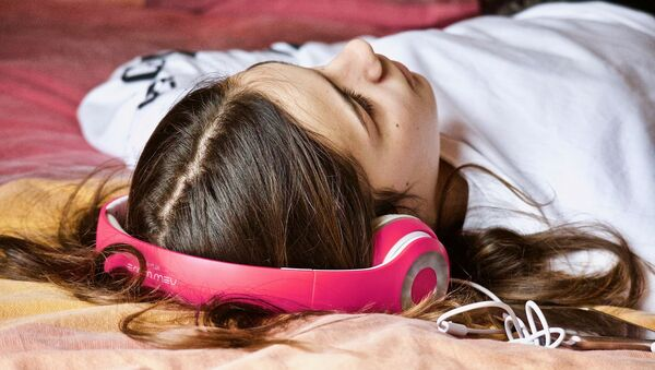 Девушка слушает музыку в наушниках, архивное фото - Sputnik Беларусь