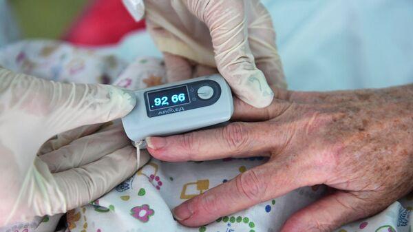 Врач работает с пациентом в палате госпиталя для больных коронавирусной инфекцией - Sputnik Беларусь