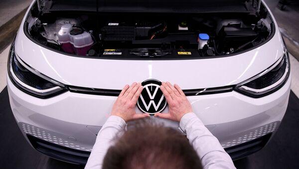 Рабочий устанавливает логотип VW на электромобиле Volkswagen ID.3 на сборочном конвейере автозавода Volkswagen - Sputnik Беларусь