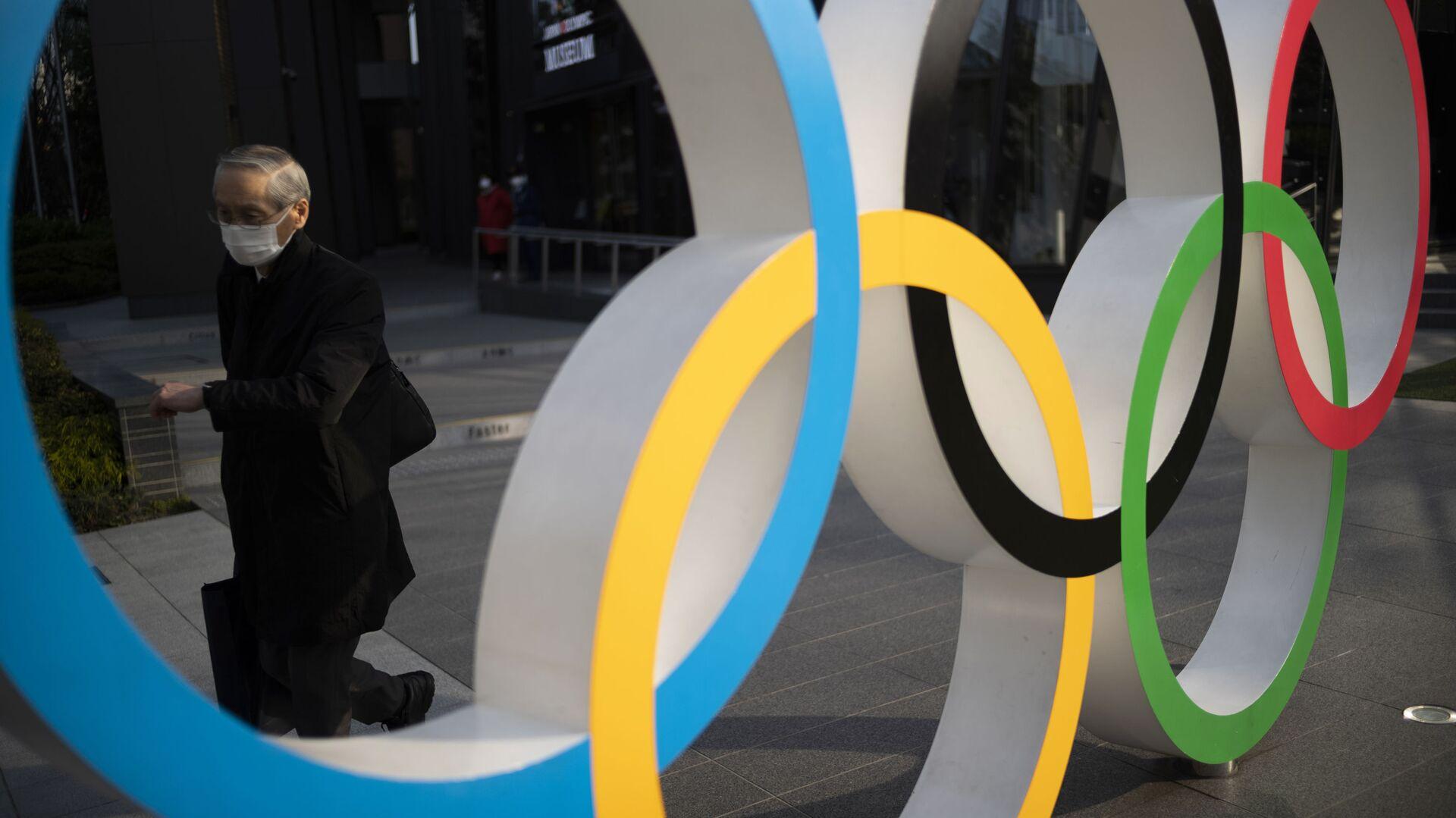 Мужчина идет мимо олимпийских колец, установленных в Японском олимпийском музее в Токио - Sputnik Беларусь, 1920, 27.05.2021