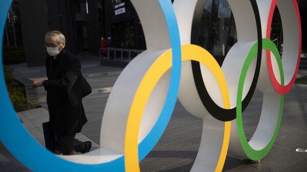 Мужчина идет мимо олимпийских колец, установленных в Японском олимпийском музее в Токио - Sputnik Беларусь