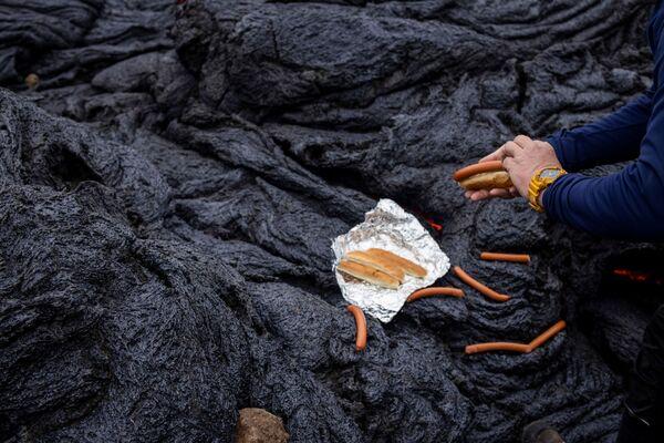 Мужчина готовит хот-доги прямо на горячей вулканической лаве после извержения в Исландии - Sputnik Беларусь